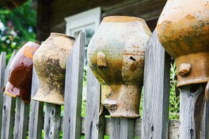 Old broken clay jugs on wooden fence