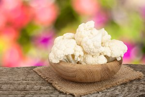 Piece of cauliflower in bowl on wooden table with blurred garden background