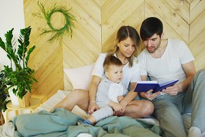 loving family of three lying on bed in morning. Family hugging and reading book