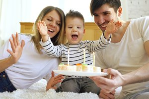 Smiling family celebrating their son birthday together before blowing candles on cake