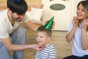 Father of happy family celebrating birthday putting on hat to his son at home