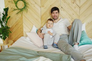 Portrait of happy handsome young father and his son lying on bed smiling and posing into camera