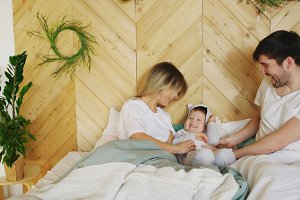 A young family with little son play on bed in the bedroom