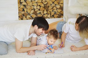 Father and mother helping their child draw picture in their living room