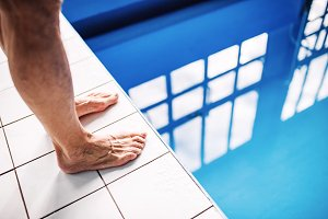 Legs of a man standing on the edge of the swimming pool.