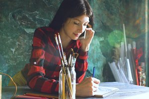 Young woman artist painting scetch on paper notebook with pencil and talking phone indoors