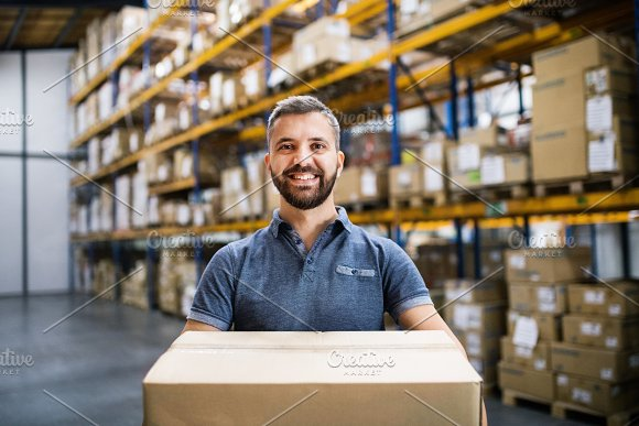 Male Warehouse Worker With A Large Box