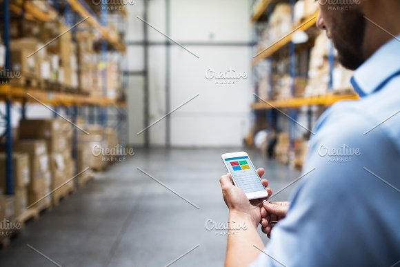 Man warehouse worker with a smartphone.