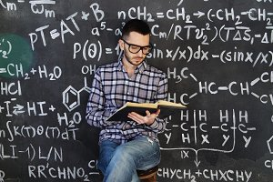 Young scientist man read book in chemical and mathematical equations wall room interior