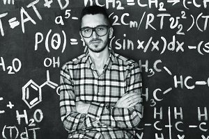 Young scientist man in laboratory with chemical and mathematical equations wall room