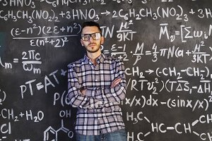Young scientist man posing in chemical and mathematical equations wall room interior