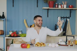 Cheerful young man using smartphone for online video chat with girlfriend while have breakfast in the morning