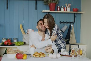 Attractive couple meet in the kitchen at breakfast time and using smartphone for social media surfing at home