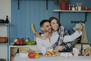 Cheerful happy couple having online video chat using smartphone in the kitchen at home in the morning