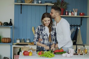 Happy young couple in the kitchen. Attractive woman cooking while her boyfriend kissing her in the morning
