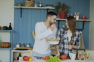 Happy young couple in the kitchen. Attractive man feeding his girlfriend while she is cooking in the morning