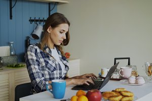 Young concentrated woman working in kitchen using laptop computer during breakfast in the morning