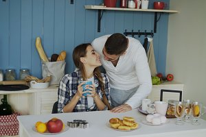 Attractive couple meet and kiss in the kitchen at breakfast time at home