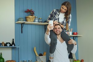 Happy young couple having fun in kitchen at home. Girl is sitting on boyfriend's neck while he taking selfie portrait on smartphone camera
