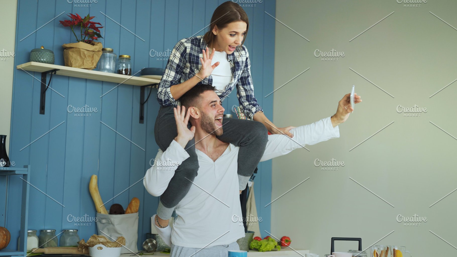Happy young couple having fun and talking online video call in the kitchen  at home  Girl is sitting on boyfriend's neck while he holding smartphone