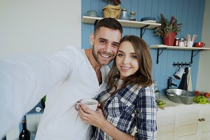 POV of Young happy couple taking selfie photos while having breakfast time in the kitchen at home