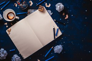 Open notepad with blank pages, crumpled paper balls, pencils, notepads and empty coffee cups on a dark background. Still life with writer workplace. Creative writing concept.