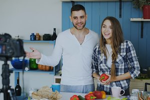 Cheerful attractive couple recording video blog about vegetarian healthy food on dslr camera in the kitchen at home