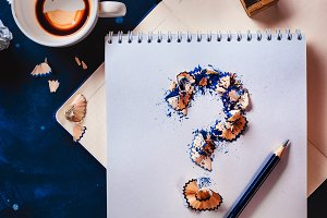 Question mark from pencil shavings with crumpled paper balls, pencils, notepads and empty coffee cups. Still life with writer workplace. Creative block concept.