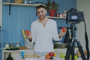 Handsome cheerful man recording video food blog about cooking on dslr camera in kitchen at home