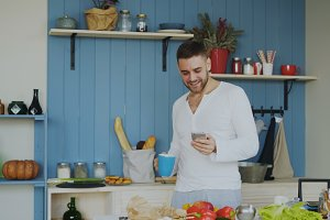 Cheerful happy man dancing and singing in kitchen while surfing social media on his smartphone at home in the morning