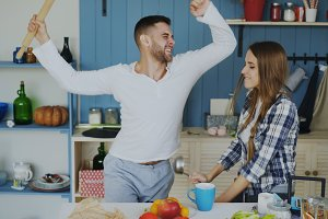 Young joyful couple have fun dancing and singing while set the table for breakfast in the kitchen at home