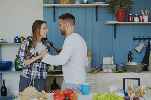 Cheerful and attractive young couple in love dancing together latin dance in the kitchen at home on holidays
