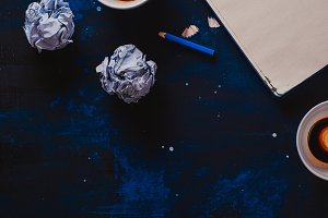 Writers block concept with open notepad, empty coffee cups, pencils and crumpled paper balls on a dark background. Creative workplace. Editing and copywriting concept.