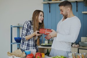 Cheerful woman surprising his boylfriend with birthday gift at home in the kitchen while he cooking breakfast