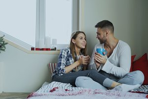 Happy young couple talking and laughing while sitting in on bed and drink coffe in the morning at home