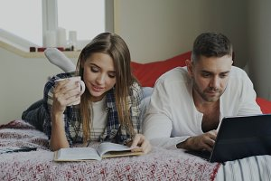 Happy couple have rest at home. Young man and woman lying in bed reading book and using laptop computer in the morning
