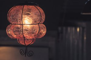 Hanging blown out glass lamp in dark