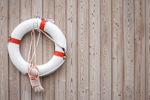 White and red life buoy on wall.