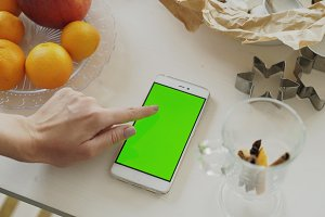 Closeup of woman's hand browsing smartphone with green screen on kitchen table at home