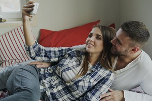 Married happy couple taking selfie portrain while lying on bed at home in the morning