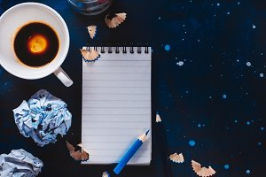 Creative writing concept with linded note paper, empty coffee cups, pencils and crumpled paper balls on a dark background. Editing and copywriting workplace.