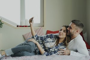 Cheerful cute and loving couple talking video call using smartphone camera and chatting with parents lying in bed at home