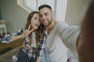 POV of Young smiling and beautiful couple take selfie portrait on smartphone camera and kiss while sitting on bed in the morning