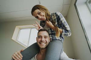 POV of happy smiling and beautiful couple take selfie portrait on smartphone camera while girl sitting on man's neck at home