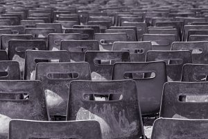 Many rows of plastic grey chairs.