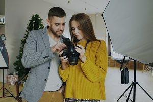 Professional photographer man showing photos on digital camera to beautiful model girl in photo studio indoors