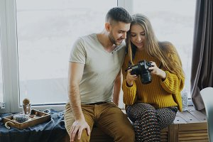 Happy smiling couple watching photos from travel on digital camera at home after vacation