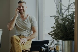 Attractive young man talking phone sitting on windowsill with laptop and camera at home