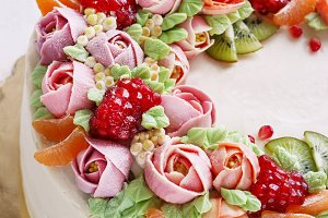 Festive cake with cream flowers and fruits on a light background