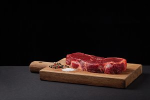 Beef steak on the wood black background with free space for text design or logotype menu restaurant. Horizontal photo. Food background. Black text area. Copy space